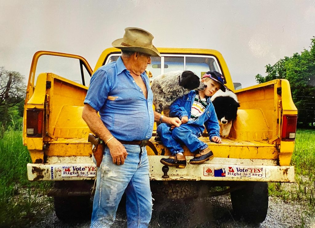 A grandfather and his grandson on the bed of their truck